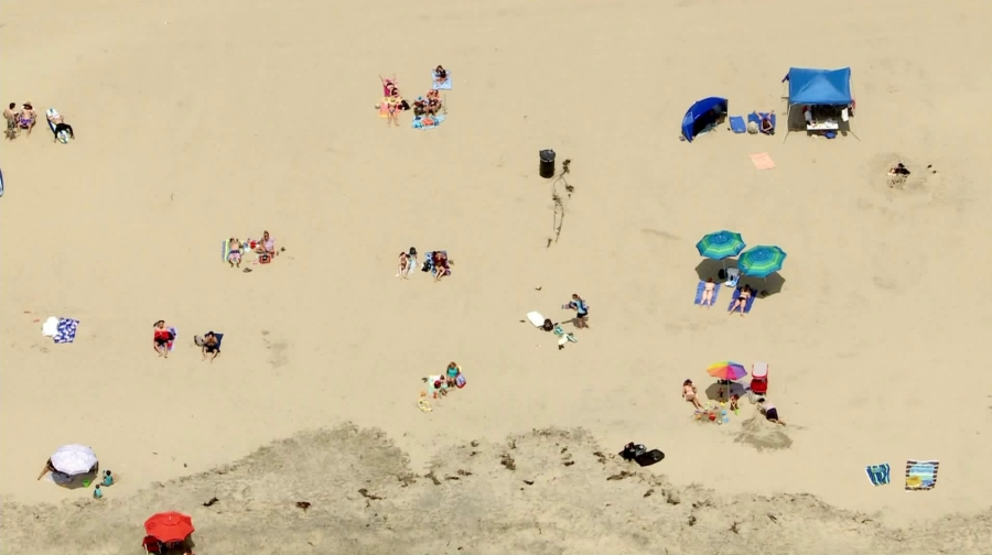 People lounge on the sand in Huntington Beach despite ongoing coronavirus orders mandating beachgoers stay active on May 7, 2020. (Credit: KTLA)