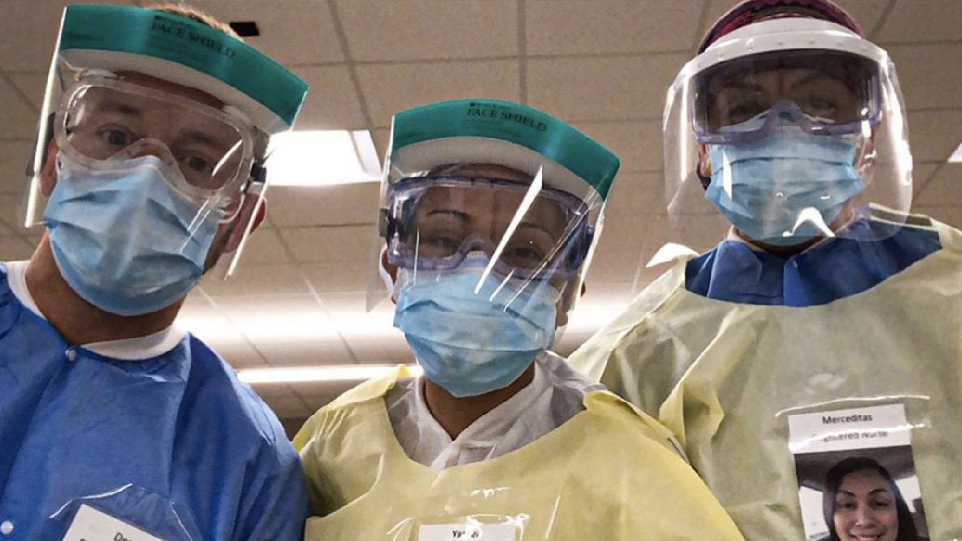 Health care workers wearing photos of themselves outside of their PPE to help put patients at ease. (Derek DeVault)