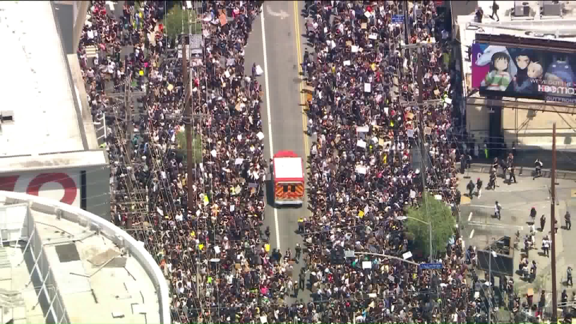 An ambulance vehicle is surrounded by dense crowds of protesters as it drives down a street in L.A.'s Fairfax District on May 30, 2020. Thousands in Los Angeles have joined nationwide protests over the death of George Floyd in Minneapolis. (KTLA)