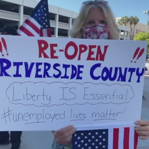 A woman participates in a protest outside the Riverside County Administrative Center while the Board of Supervisors considered lifting some coronavirus restrictions on May 5, 2020. (Credit: KTLA)