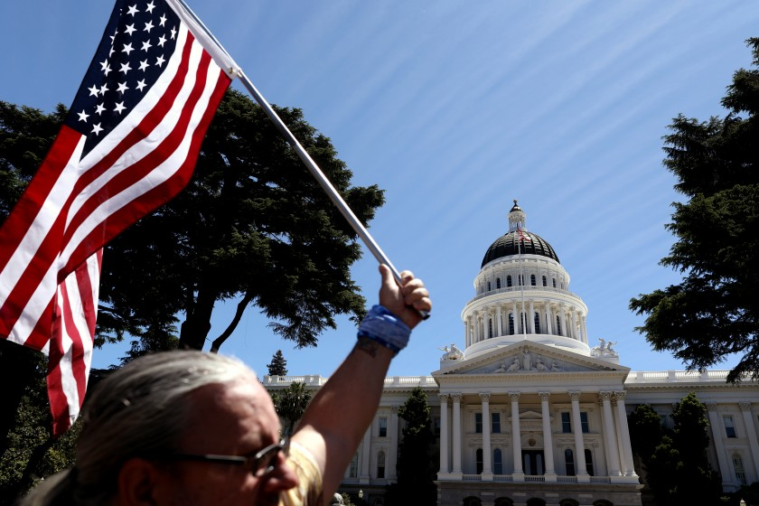 """A crowd of roughly 2,000 gathered on May 23, 2020 for """"Liberty Fest,"""" hosted by the Freedom Angels, outside the closed California Capitol in Sacramento. (Gary Coronado / Los Angeles Times)"""