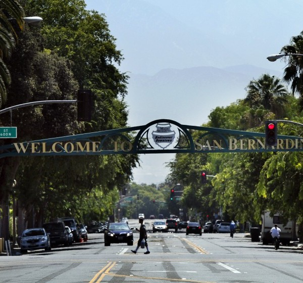 A pedestrian walks under a sign for the city of San Bernardino in this undated photo. (Irfan Khan / Los Angeles Times)