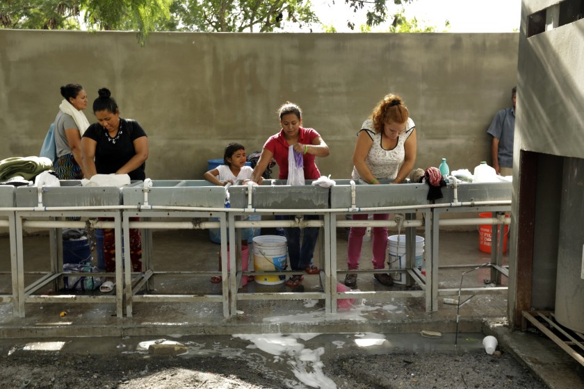 "Migrants are seen in an undated photo washing their clothes at the Matamoros refugee camp, where hundreds of asylum seekers are waiting for U.S. court hearings under the ""Remain in Mexico"" program. (Carolyn Cole / Los Angeles Times)"