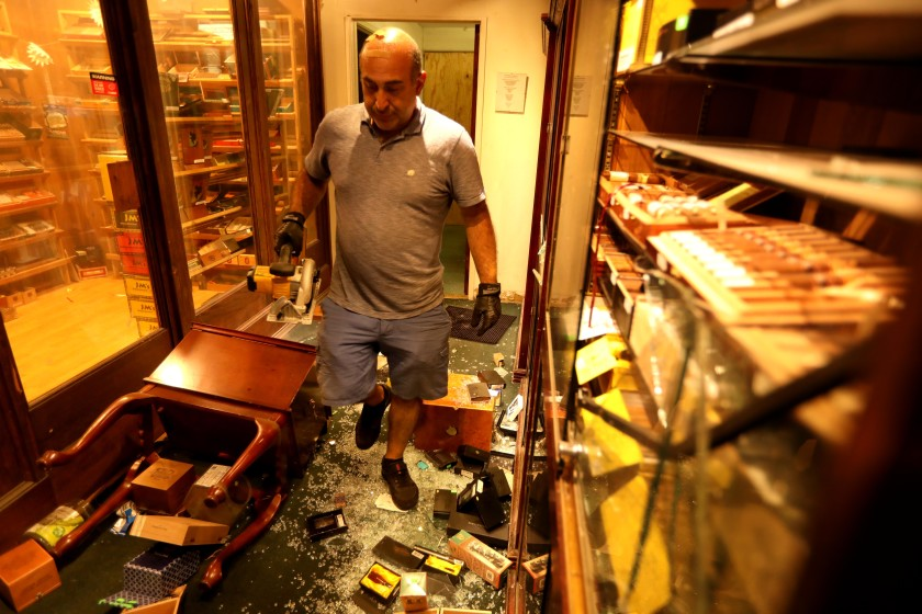 Moe, owner of Santa Monica Tobacco, walks through his business, which was looted and burned Sunday in Santa Monica on May 31, 2020.(Genaro Molina / Los Angeles Times)