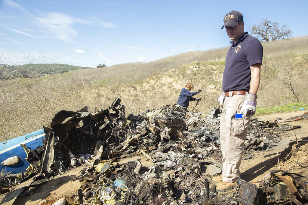 In this Jan. 27, 2020, file photo, provided by the National Transportation Safety Board, NTSB investigators Adam Huray, right, and Carol Hogan examine wreckage as part of the NTSB's investigation of a helicopter crash near Calabasas, Calif. Federal investigators said Wednesday, June 17, 2020, that the pilot of the helicopter that crashed in thick fog, killing Kobe Bryant and seven other passengers, reported he was climbing when he actually was descending. (James Anderson/National Transportation Safety Board via AP, File)
