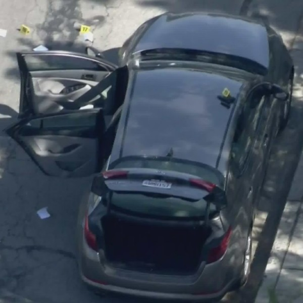 Evidence markers surround a vehicle after an occupant was wounded in a shootout with Pomona police in Montclair on June 29, 2020. (KTLA)