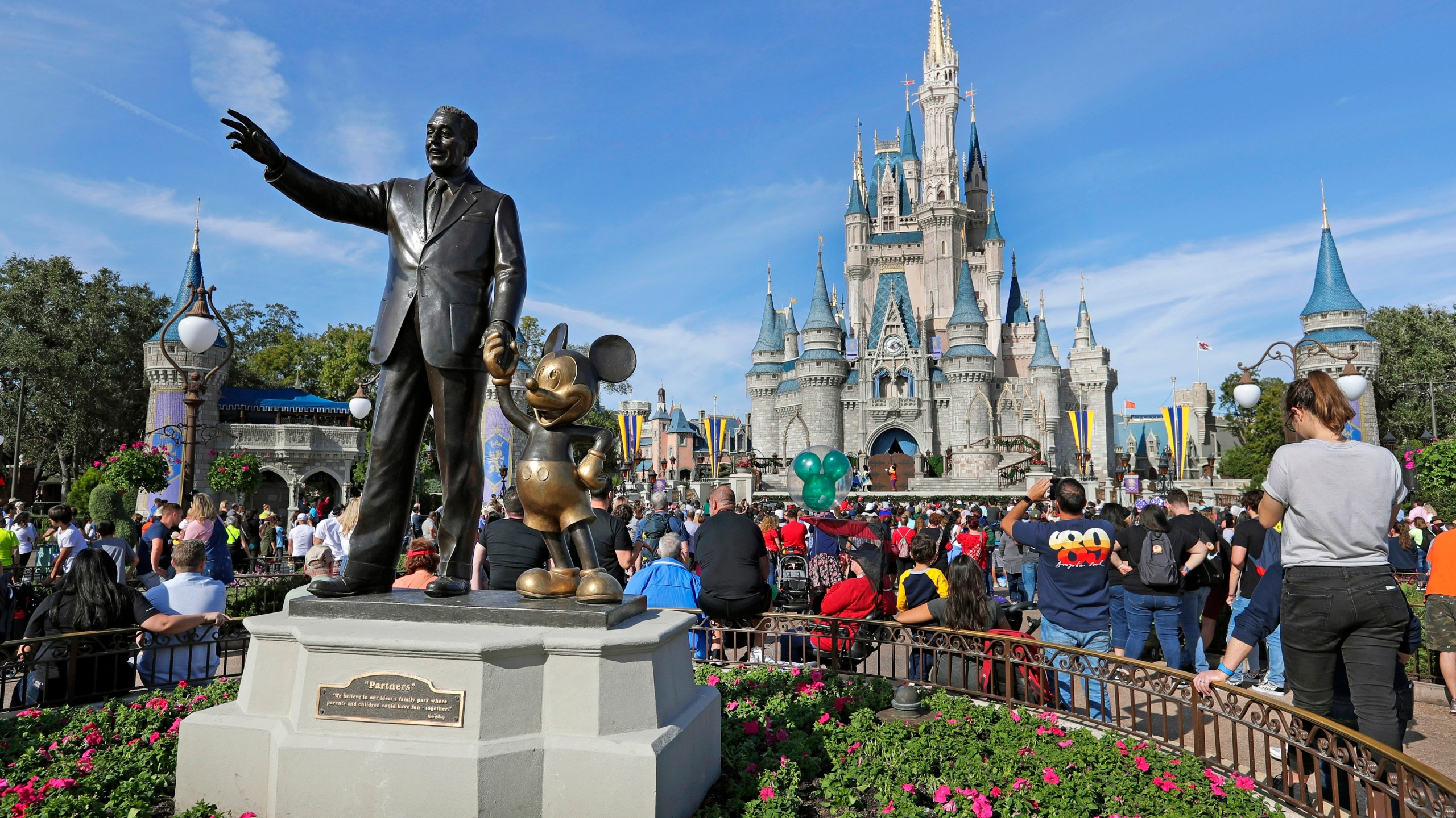 In this Jan. 9, 2019 photo, guests watch a show near a statue of Walt Disney and Micky Mouse in front of the Cinderella Castle at the Magic Kingdom at Walt Disney World in Lake Buena Vista, part of the Orlando area in Fla. SeaWorld and Universal Orlando reopened earlier June 2020, while Disney plans to reopen in phases starting July 11, 2020.(AP Photo/John Raoux, File)