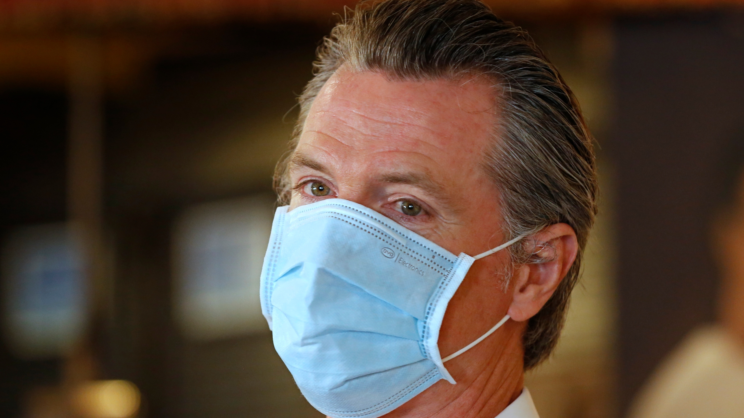 In this June 19, 2020, file photo, California Gov. Gavin Newsom, wears a face mask as he answers a reporter's question during his visit to the Queen Sheba Ethiopian Cuisine restaurant in Sacramento, Calif. Newsom implored people Monday, June 22, 2020, to wear face coverings to protect against the coronavirus and allow businesses to safely open after several days in which the state saw its highest virus hospitalizations and number of infections to date. (AP Photo/Rich Pedroncelli, Pool)