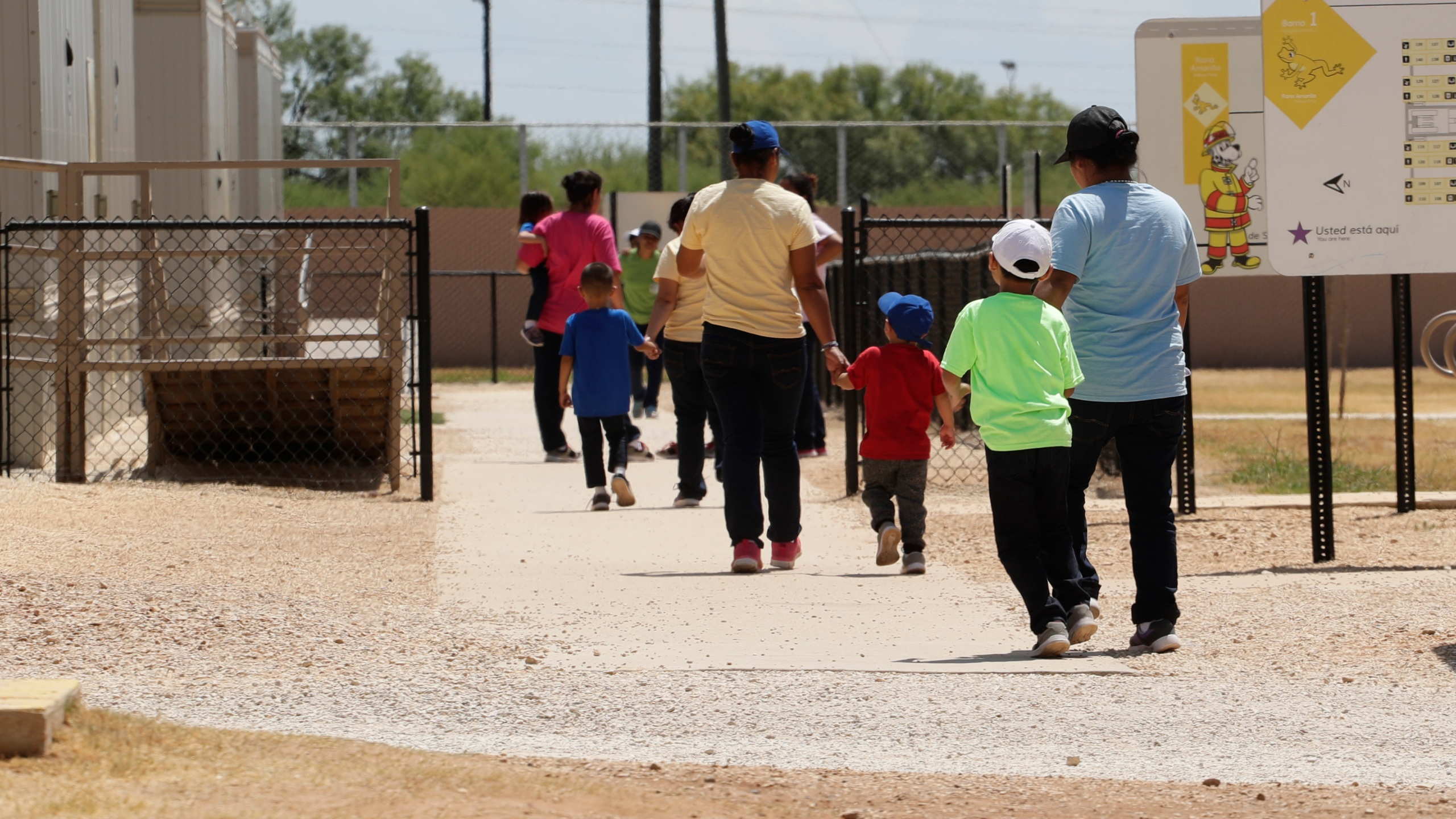 Immigrants seeking asylum hold hands as they leave a cafeteria at the ICE South Texas Family Residential Center in Dilley, Texas on Aug. 23, 2019. (AP Photo/Eric Gay, File)