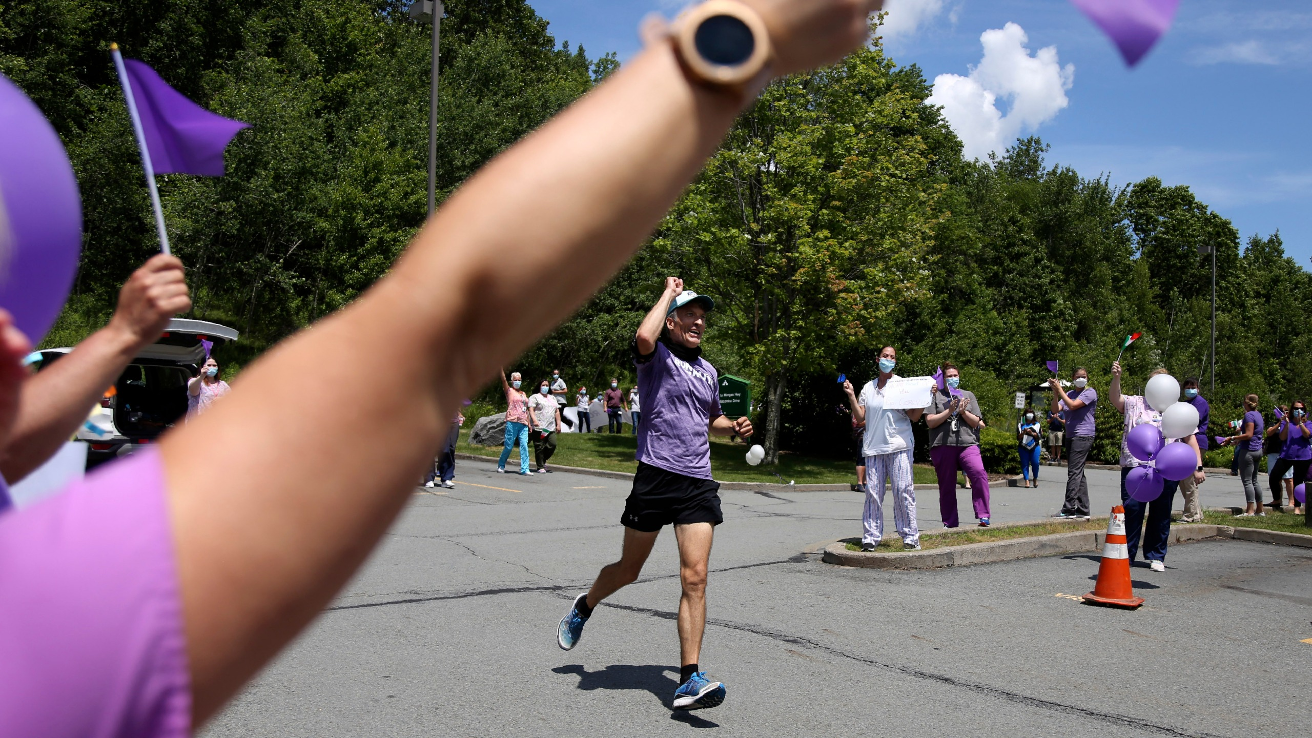 Nursing home workers cheer as Corey Cappelloni completes his seventh ultramarathon in seven days in Scranton, Pa., Friday, June 19, 2020. Cappelloni ran roughly 218 miles from Washington, D.C., to Scranton to visit his 98-year-old grandmother and raise awareness for older adults in isolation amid the coronavirus pandemic. (AP Photo/Jessie Wardarski)