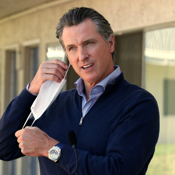 Gov. Gavin Newsom removes his face mask before giving an update on the state's initiative to provide housing for homeless Californians to help stem the coronavirus, during a visit to a Motel 6 participating in the program in Pittsburg. (AP Photo/Rich Pedroncelli, Pool)