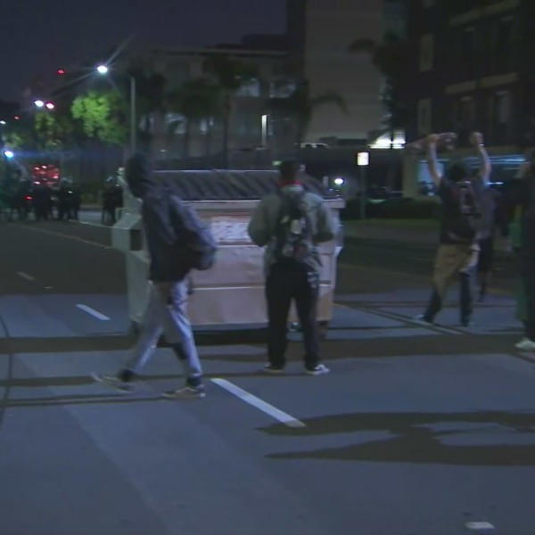 Racial justice protesters who remain in the street past a citywide curfew engage in a standoff with police in Santa Ana on June 22, 2020. (KTLA)