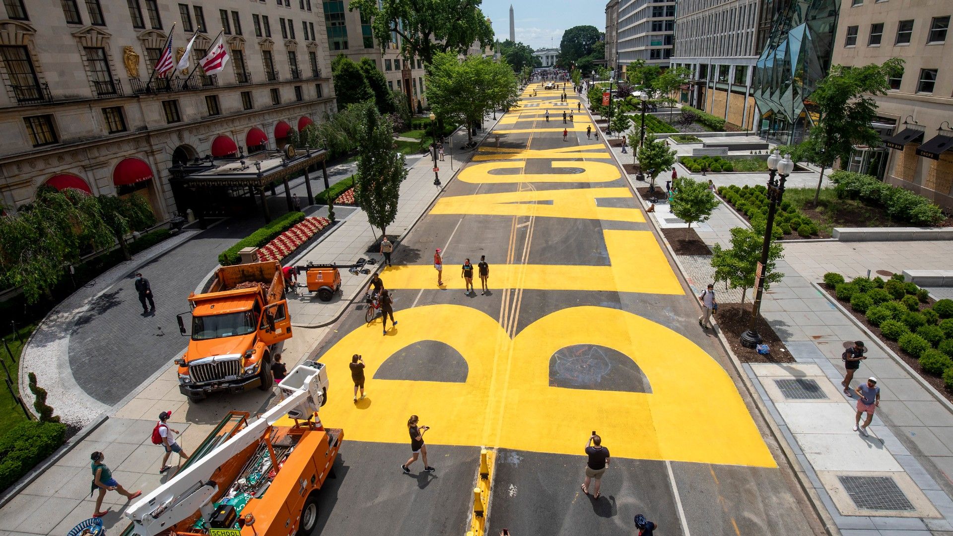 """People walk down 16th street after volunteers, with permission from the city, painted """"Black Lives Matter"""" on the street near the White House on June 05, 2020, in Washington, DC. (Tasos Katopodis/Getty Images)"""