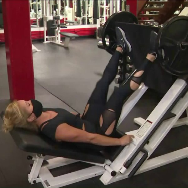 A woman wearing a face mask works out a gym in Hollywood on June 12, 2020. (KTLA)