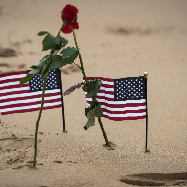 Two roses and two US flags are pictured on Omaha beach in Saint-Laurent-sur-Mer, Normandy, on June 5, 2019, on the sidelines of the D-Day commemorations marking the 75th anniversary of the World War II Allied landings in Normandy. (JOEL SAGET/AFP via Getty Images)
