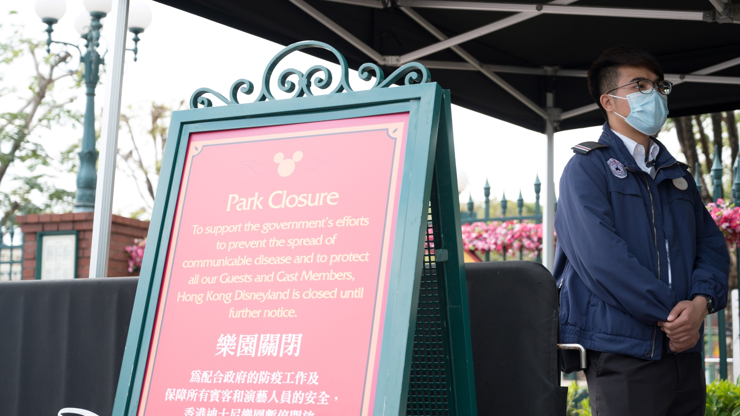 A member of staff wearing a mask stands next to a sign announcing the park's closure at Hong Kong Disneyland in Hong Kong on January 26, 2020, after it announced it was shutting its doors until further notice over a deadly virus outbreak in central China. (Ayaka MCGILL / AFP/Getty Images)
