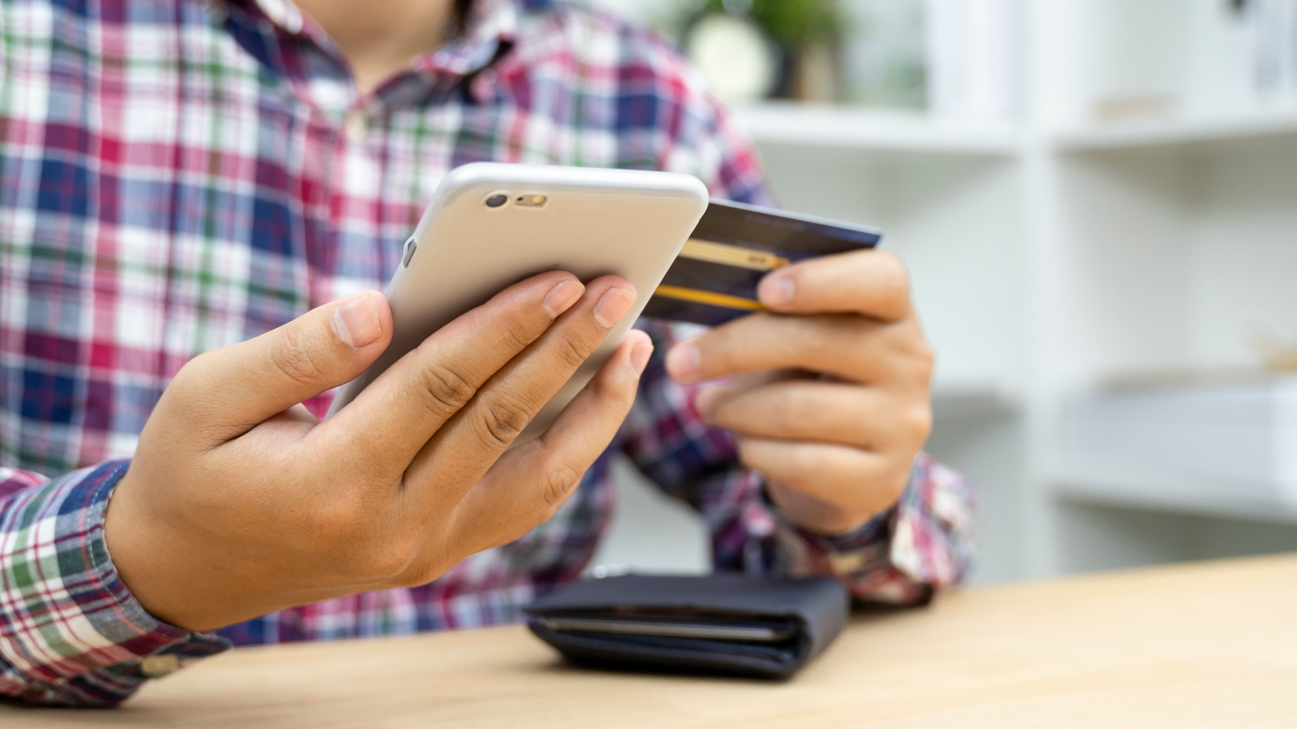 This file photo shows a man holding a credit card and using a phone. (Getty Images)