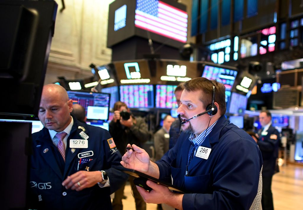 Traders work during the closing bell at the New York Stock Exchange (NYSE) on March 18, 2020 at Wall Street in New York City. - Wall Street stocks plunged again March 18, 2020 as the economic toll from the coronavirus mounts and economists warn of a deep recession.