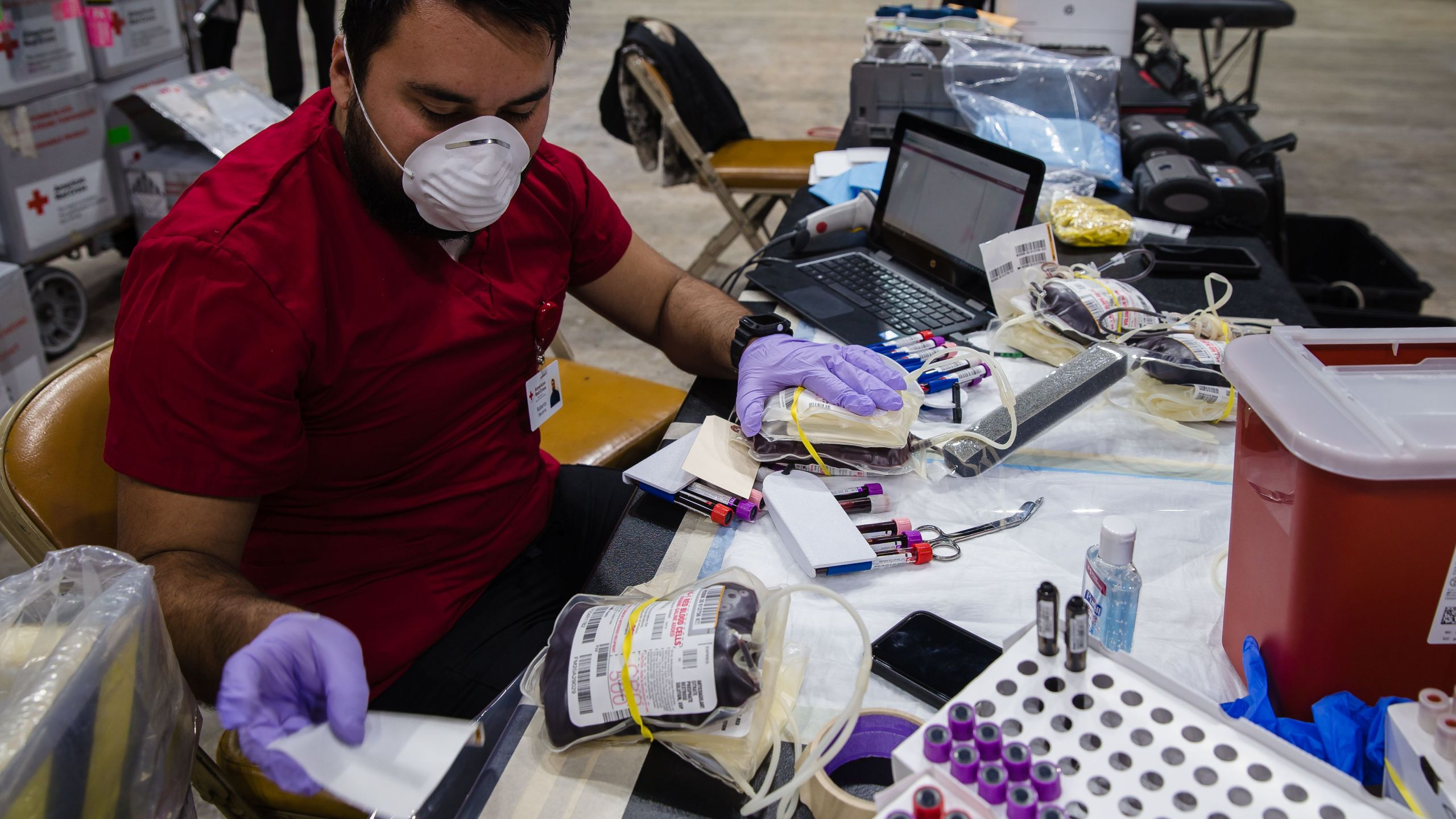 A Red Cross worker scans the bags and tubes filled with blood at Pechanga Arena on April 14, 2020 in San Diego, California. (ARIANA DREHSLER/AFP via Getty Images)