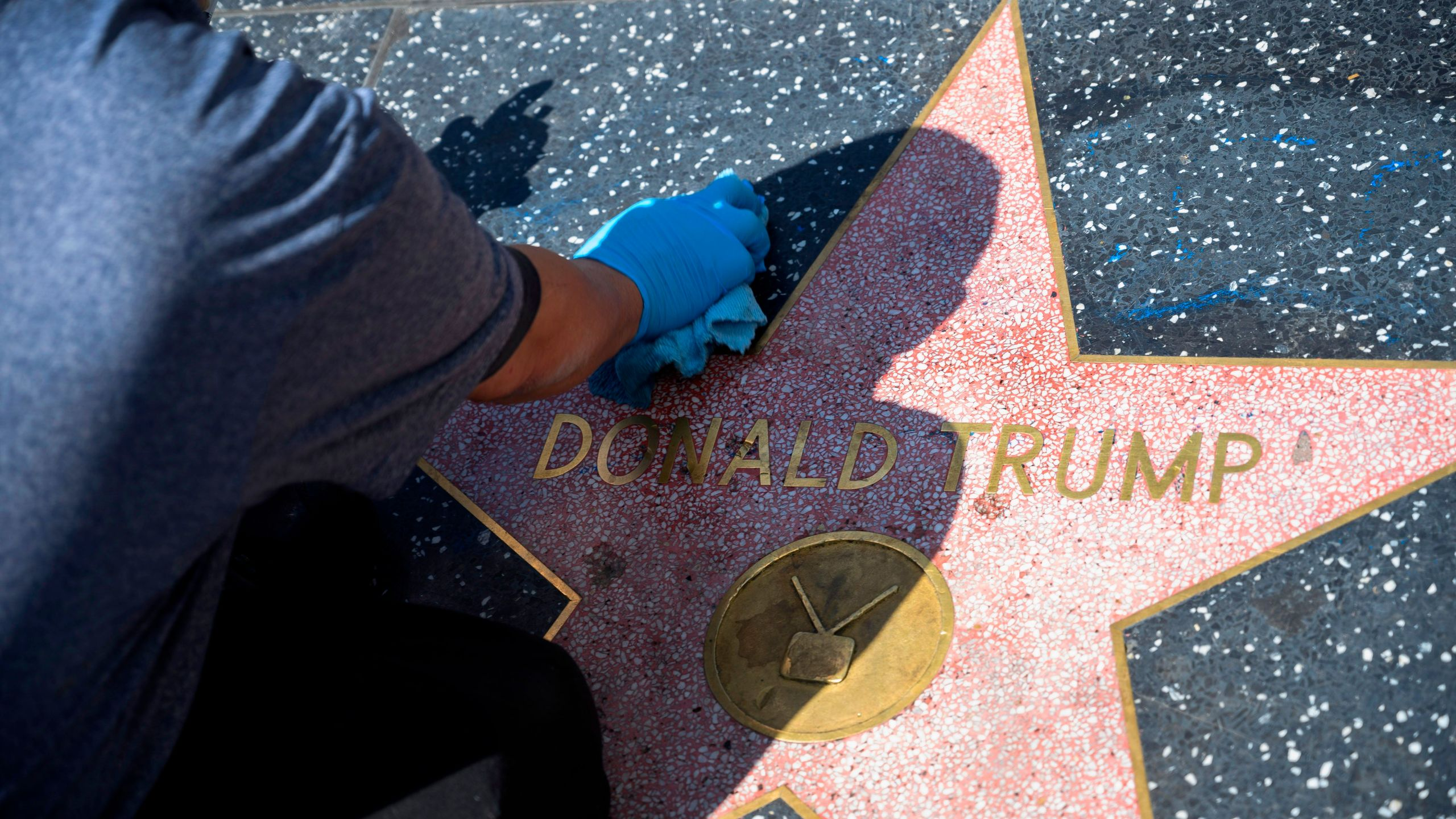 A maintenance worker uses cleaning product to remove graffiti after Donald Trump's star on the Hollywood Walk of Fame was defaced on April 23, 2020 (ROBYN BECK/AFP via Getty Images)