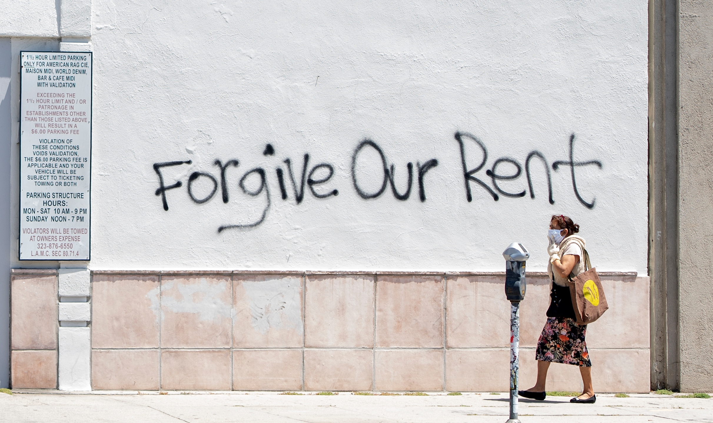 A woman wearing a mask walks past a wall bearing a graffiti asking for rent forgiveness on La Brea Ave amid the COVID-19 pandemic on May 1, 2020. (Valeria Macon /AFP / Getty Images)