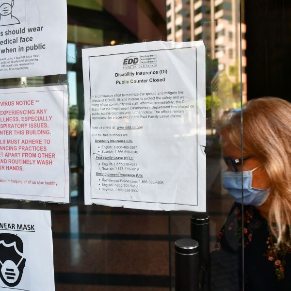 A woman wearing a face mask enters a building where the Employment Development Department has its offices in Los Angeles on May 4, 2020. (FREDERIC J. BROWN/AFP via Getty Images)