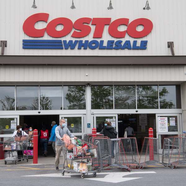 Shoppers walk out with full carts from a Costco store in Washington, DC, on May 5, 2020. (NICHOLAS KAMM/AFP via Getty Images)