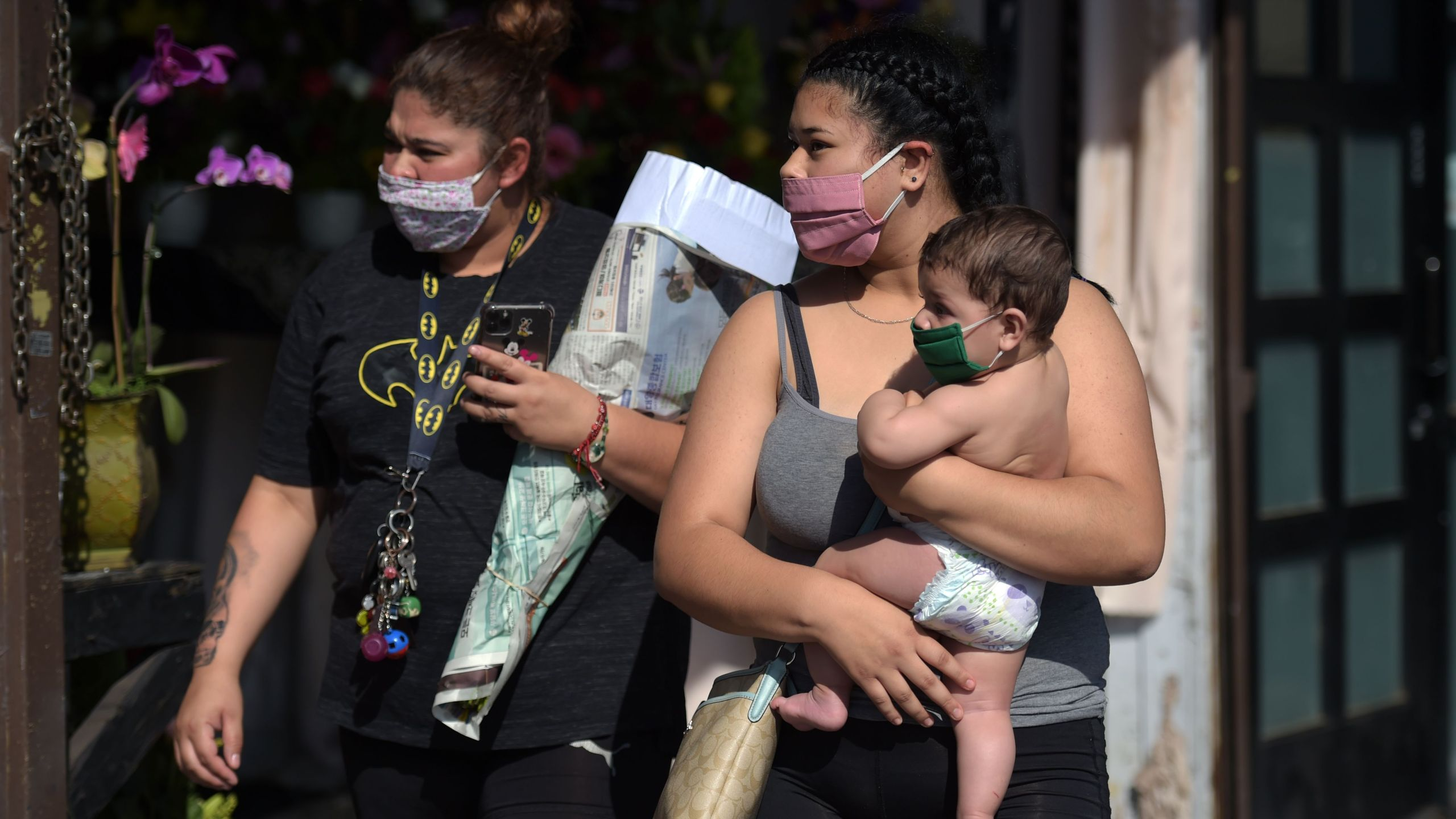A woman holds a child while people shop at the Los Angeles Flower District ahead of Mother's Day on May 8, 2020. (AGUSTIN PAULLIER/AFP via Getty Images)