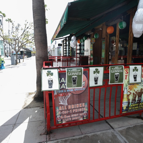 A man walks past a closed bar advertising Saint Patrick's Day on March 17, 2020, in Santa Monica. (Mario Tama/Getty Images)