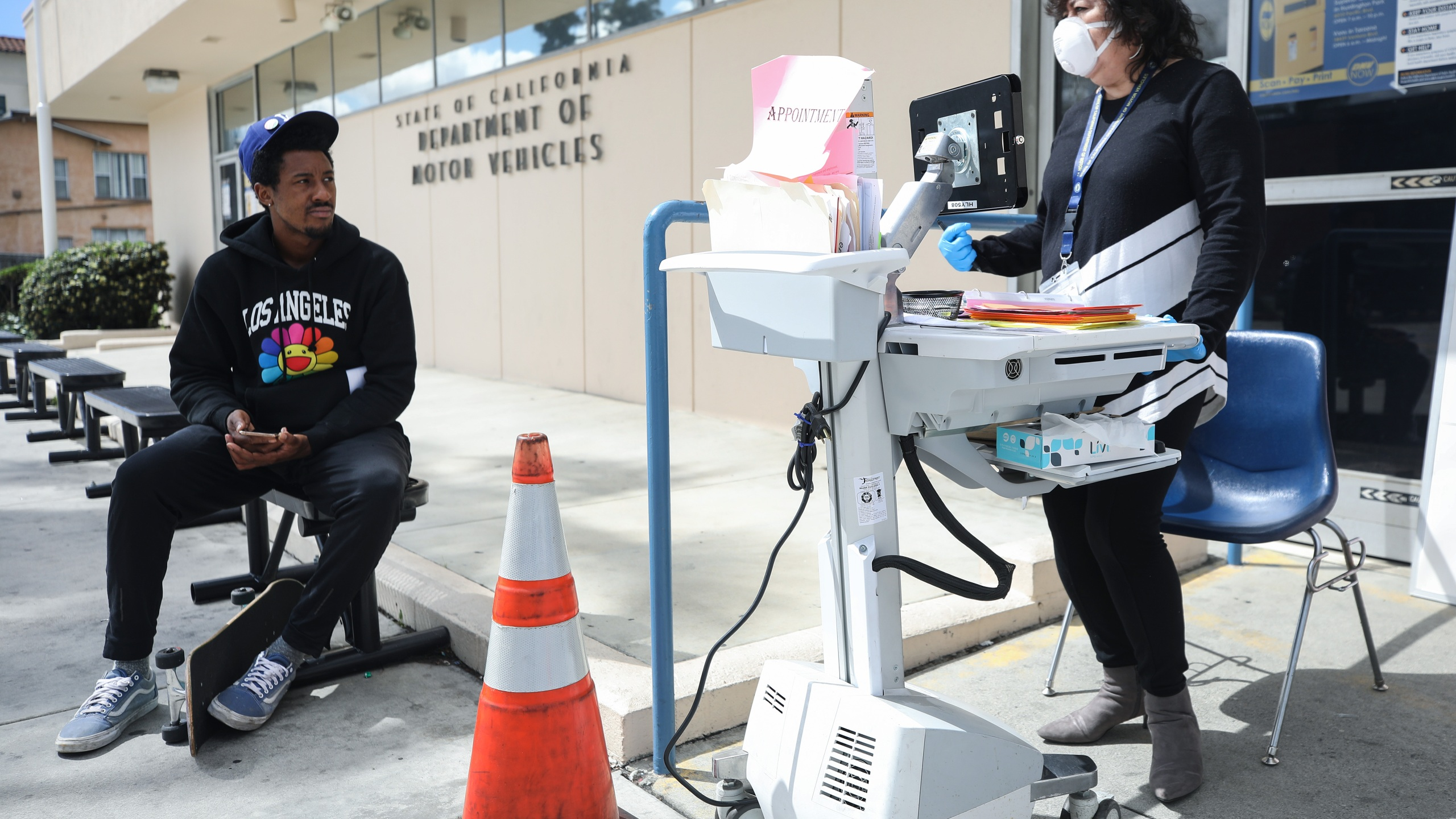 A Department of Motor Vehicles worker speaks with a man who did not have an appointment at an appointment desk in front of the DMV building, with a cone used to implement social distancing, on March 23, 2020 in Los Angeles. (Mario Tama/Getty Images)