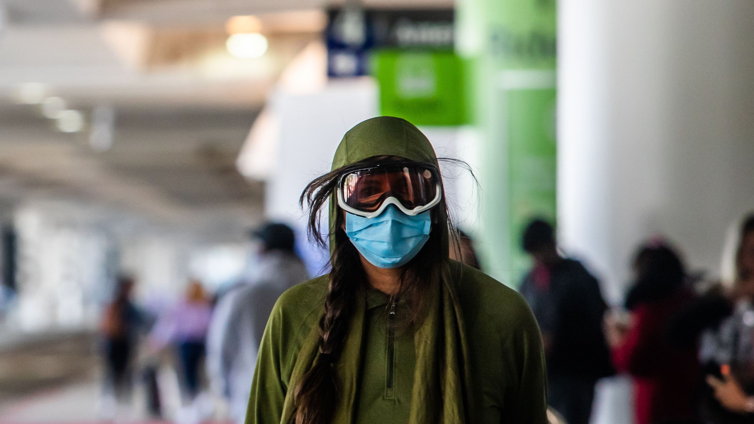 A woman wearing a face mask and goggles walks at LAX airport at the start of the Memorial Day holiday weekend during the novel coronavirus, COVID-19, pandemic in Los Angeles, California on May 22, 2020. (APU GOMES/AFP via Getty Images)