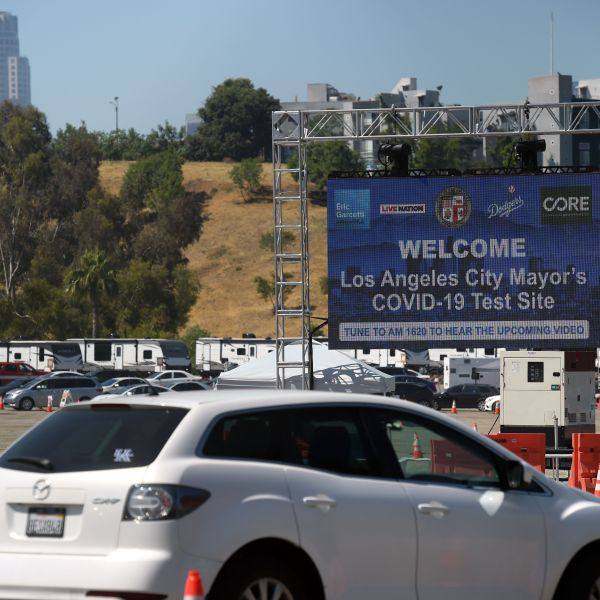 People line up in their cars at a drive-through coronavirus testing site at the Dodgers Stadium parking lot. (AGUSTIN PAULLIER/AFP via Getty Images)