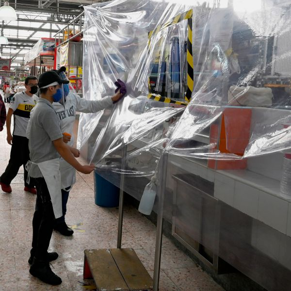 Two workers clean the plastic protection of a store to prevent the spread of COVID-19 at the Martinez de la Torre Market in Mexico City on May 28, 2020. (ALFREDO ESTRELLA/AFP via Getty Images)
