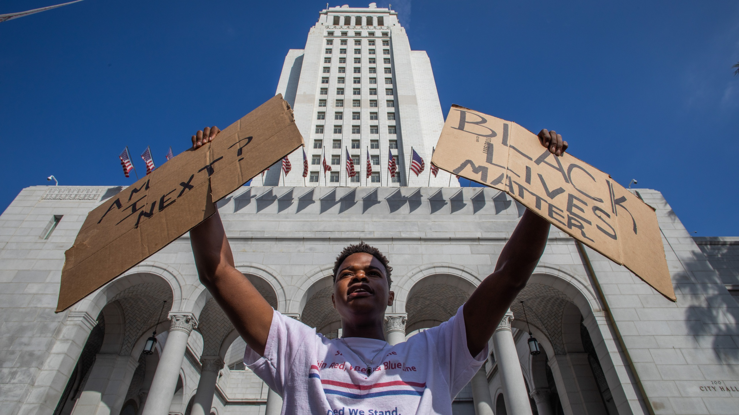 "A demonstrator holds two signs, one that says ""Am I next? and another that says ""Black Lives Matter,"" in front of Los Angeles City Hall on May 29, 2020. (Apu Gomes/Getty Images)"