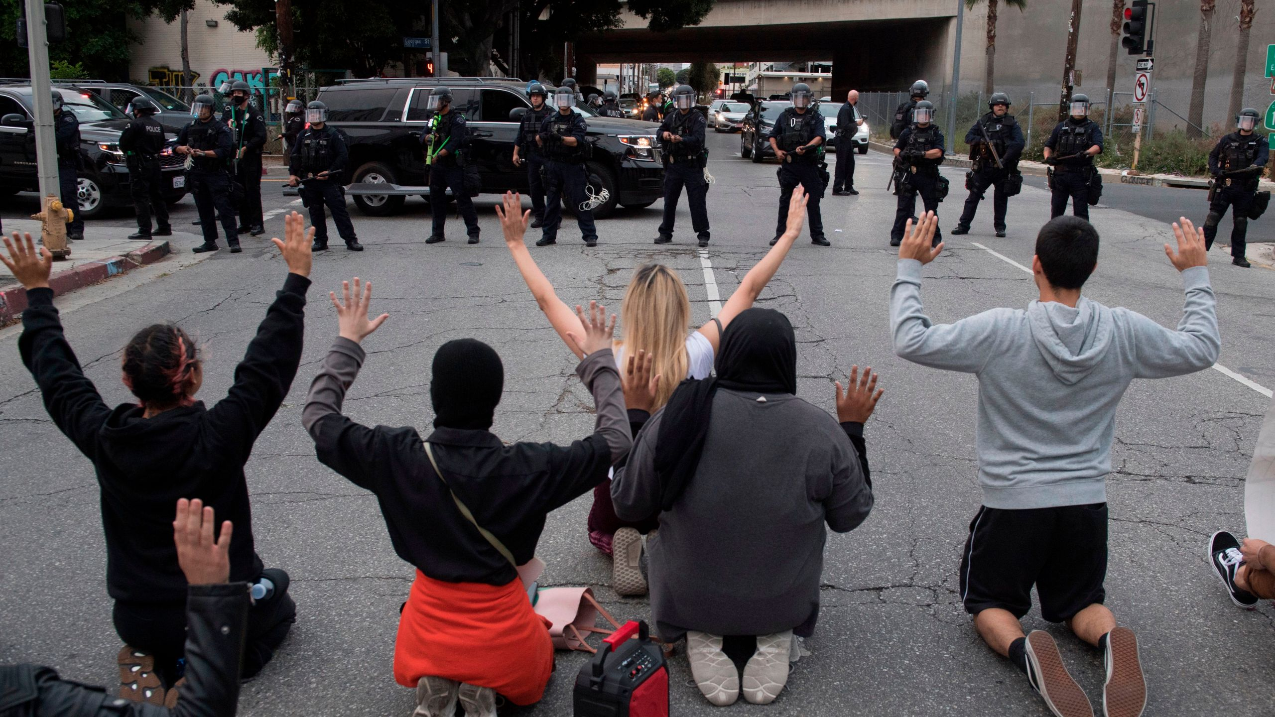 Demonstrators face a row of police as they block a road leading to the 110 freeway to protest the death of George Floyd, in downtown Los Angeles on May 29, 2020.(MARK RALSTON/AFP via Getty Images)