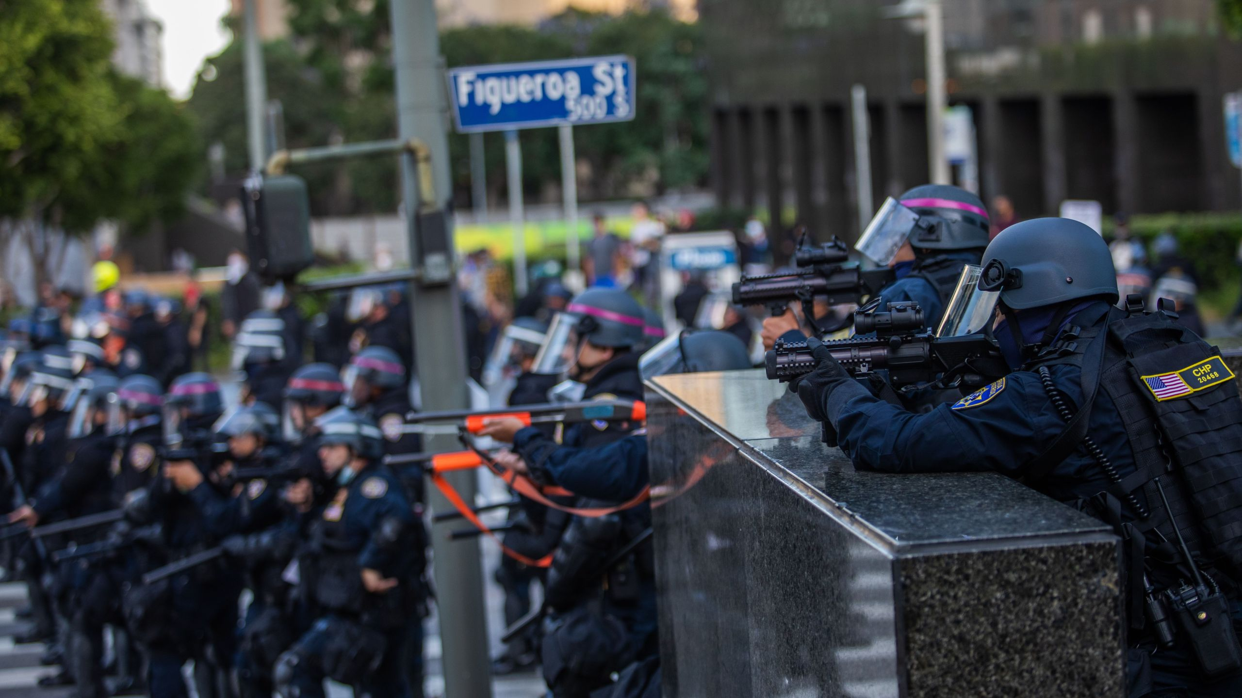 Police stand in a skirmish line while demonstrators after they throw stones in their direction in downtown Los Angeles on May 30, 2020. (APU GOMES/AFP via Getty Images)