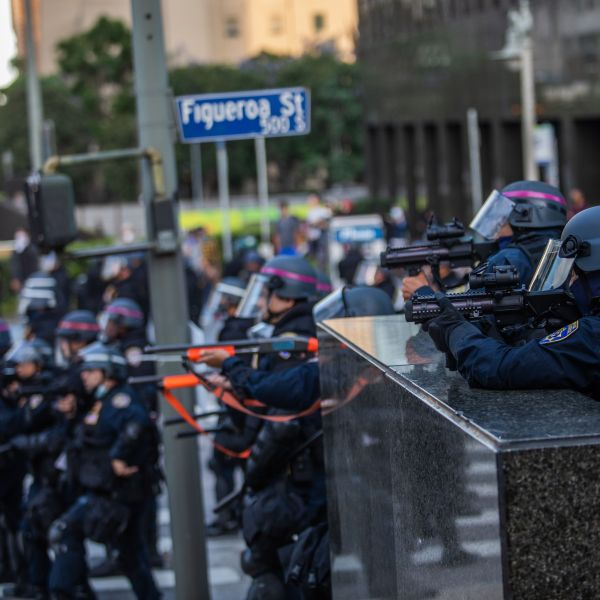 Police stand in a skirmish line while demonstrators after they throw stones in their direction in downtown Los Angeles on May 30, 2020. During another incident in the area that day, an officer fired at a man who police say was driving towards officers. (APU GOMES/AFP via Getty Images)