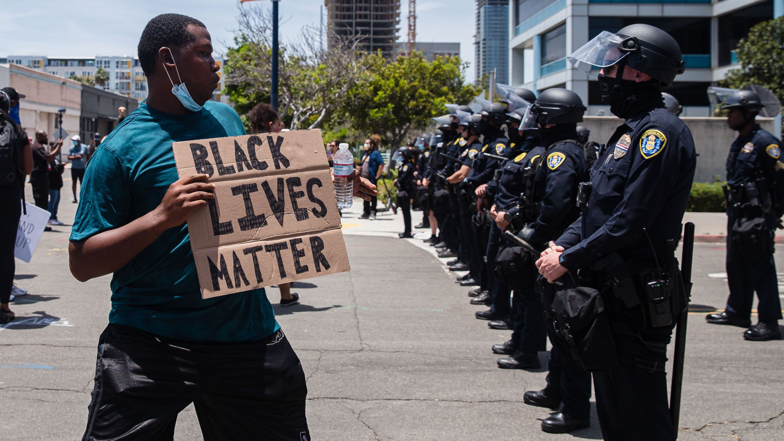 A man holds a Black Lives Matter sign in front of police in downtown San Diego on May 31, 2020. (ARIANA DREHSLER / AFP / Getty Images)