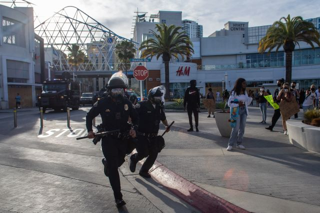 Police officers run in downtown Long Beach on May 31, 2020 during a protest against the death of George Floyd. (Apu GOMES / AFP) (Photo by APU GOMES/AFP via Getty Images)