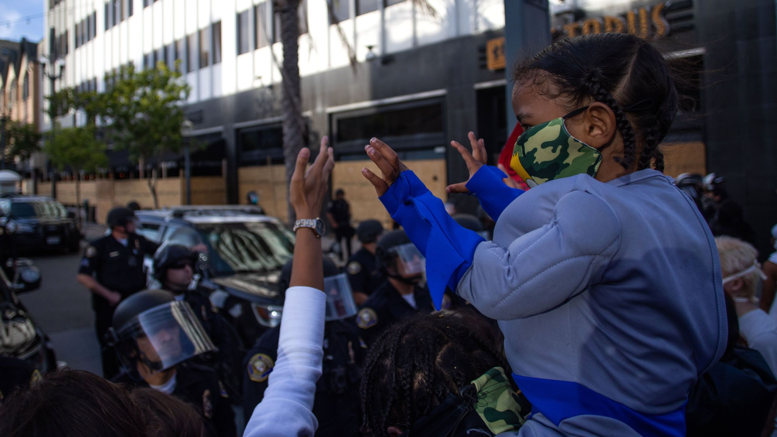 A child holds up his hands in front of a row of police officers in downtown Long Beach on May 31, 2020 during a protest against the death of George Floyd. (APU GOMES/AFP via Getty Images)