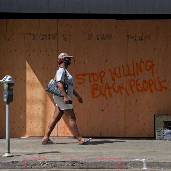 A woman walks past a boarded up store after demonstrators protested the death of George Floyd in downtown Los Angeles on May 31, 2020. (AGUSTIN PAULLIER/AFP via Getty Images)