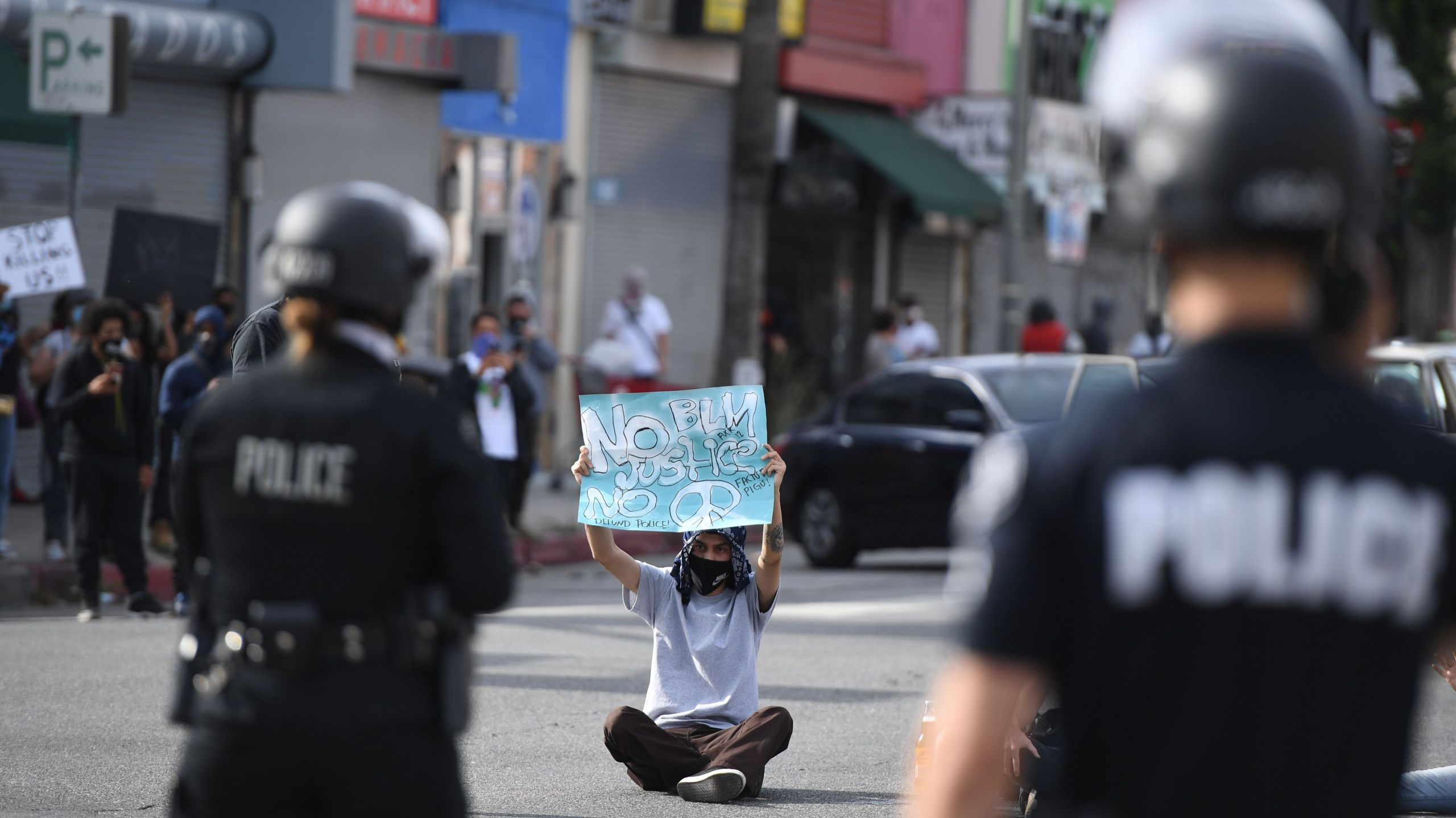 A demonstrator holds a sign as he sits in front of police in Van Nuys on June 1, 2020. (Robyn Beck / AFP / Getty Images)