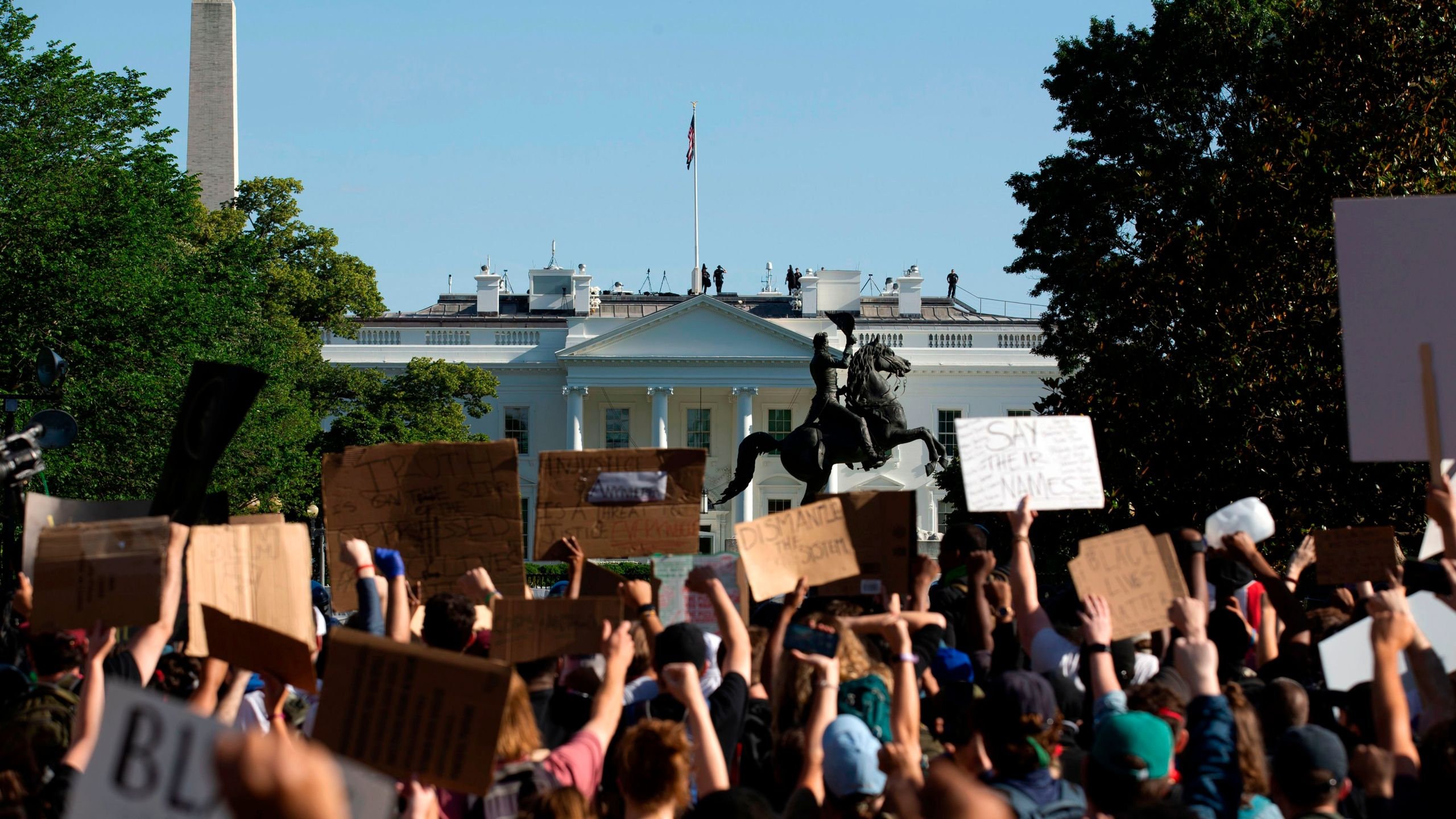 Demonstrators hold up placards protest outside of the White House, over the death of George Floyd in Washington D.C. on June 1, 2020. (Jose LUIS MAGANA/AFP via Getty Images)