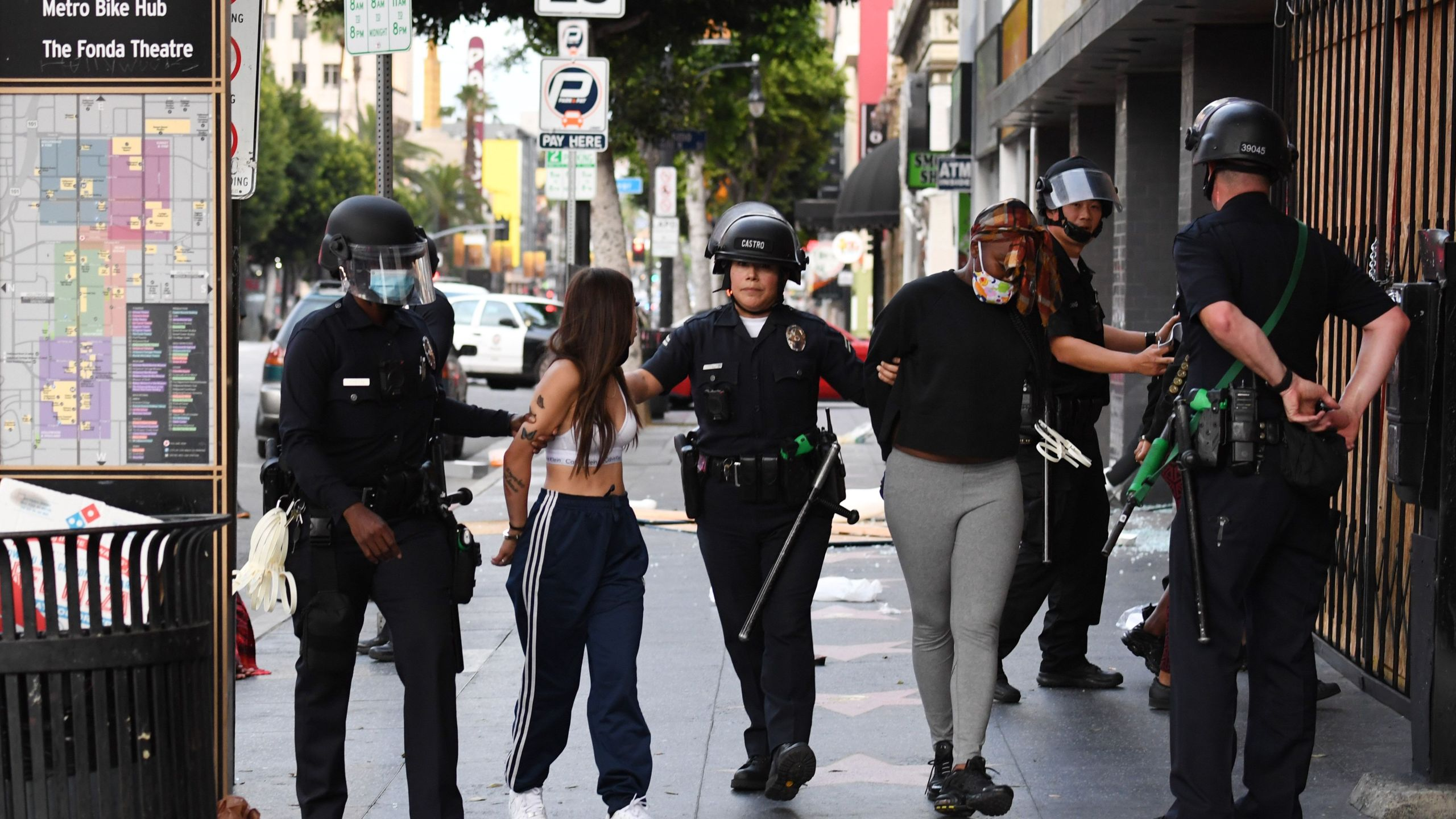 Police officers arrest people after a store was looted in Hollywood on June 1, 2020, after a third day of protests and looting throughout California. (ROBYN BECK/AFP via Getty Images)