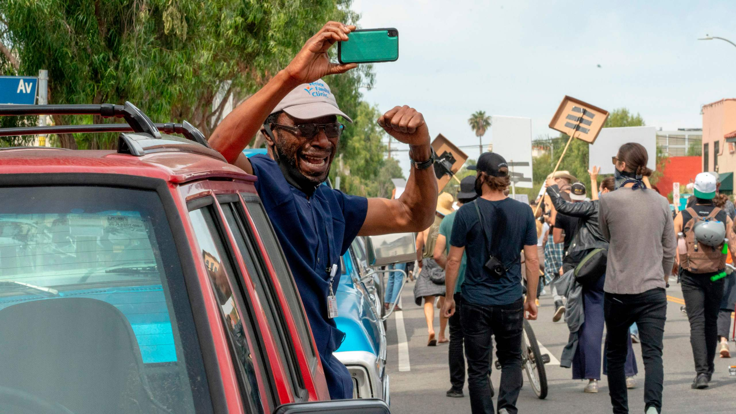 Tunde Obazee becomes emotional while taking a break from his job to cheer on marchers in Venice during a demonstration over the death of George Floyd in Los Angeles on June 2, 2020. (KYLE GRILLOT/AFP via Getty Images)
