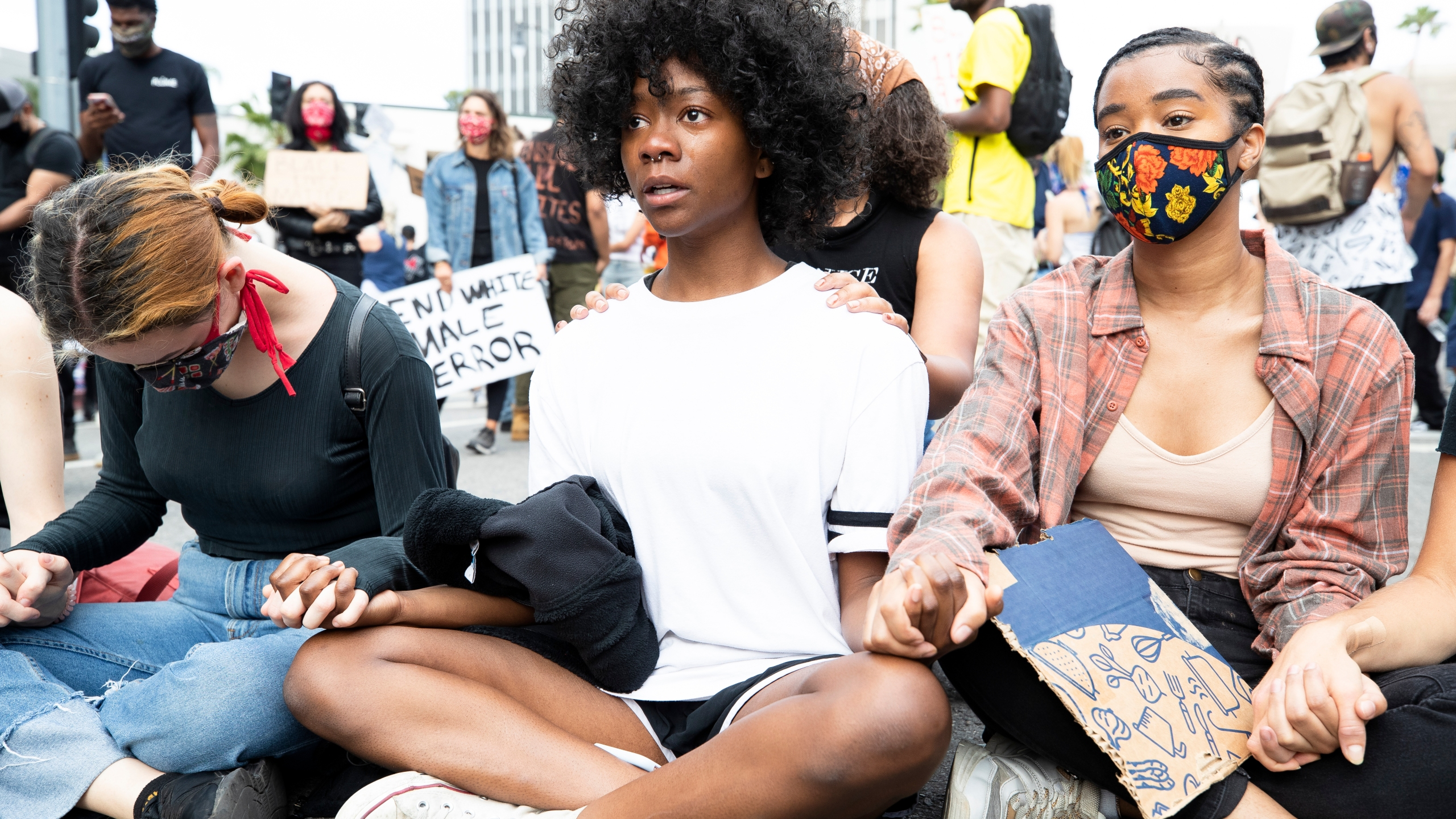 Demonstrators sit holding hands during a march on June 2, 2020 in Los Angeles. (Brent Stirton/Getty Images)