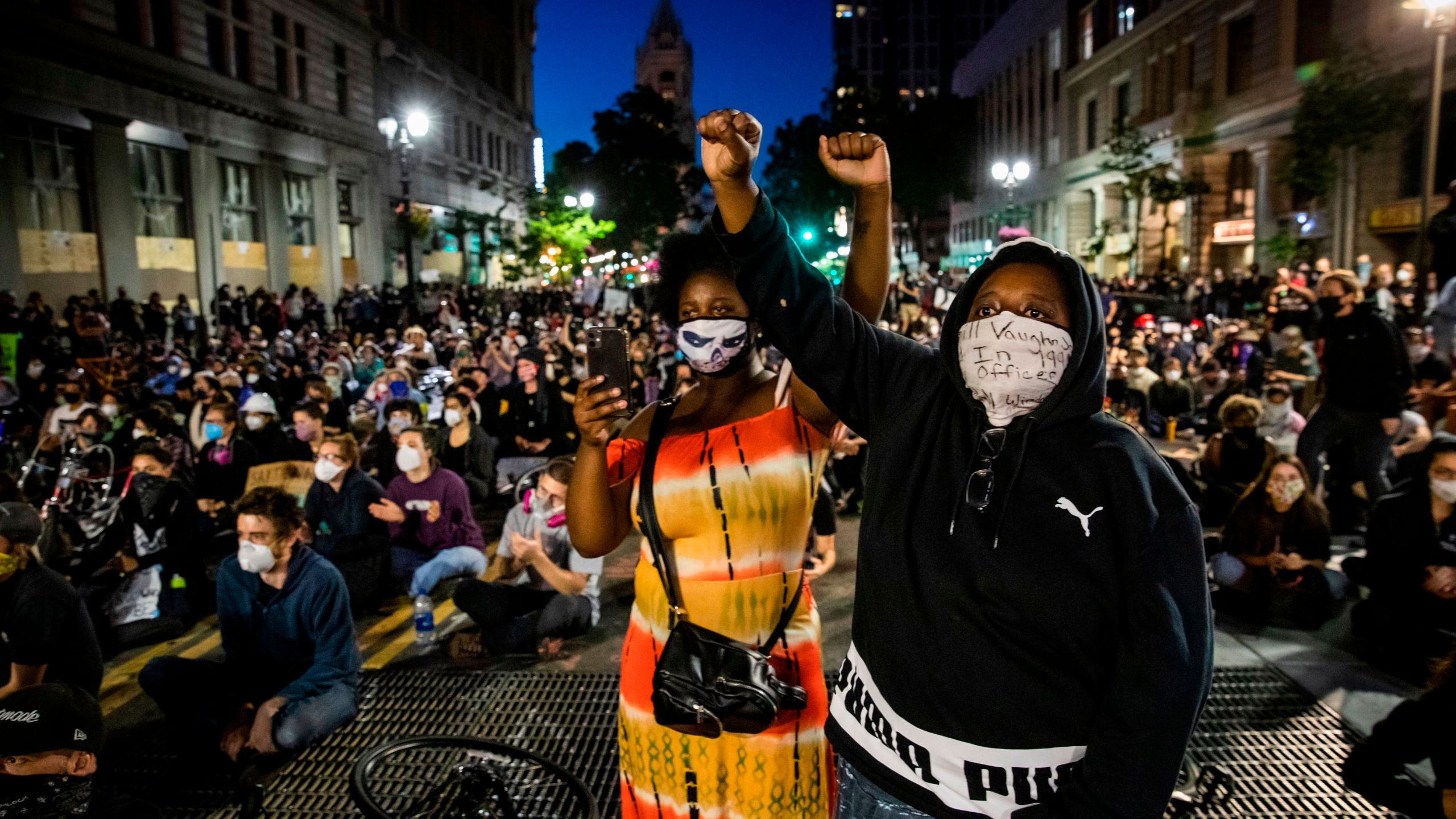 "Demonstrators raise their fists during a ""Sit Out the Curfew"" protest over the death of George Floyd, along a street in Oakland, California on June 3, 2020.(PHILIP PACHECO/AFP via Getty Images)"