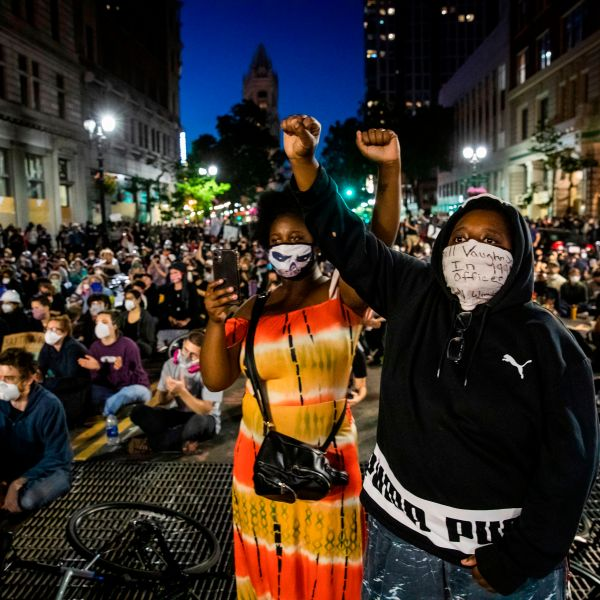 """Demonstrators raise their fists during a """"Sit Out the Curfew"""" protest over the death of George Floyd, along a street in Oakland, California on June 3, 2020.(PHILIP PACHECO/AFP via Getty Images)"""