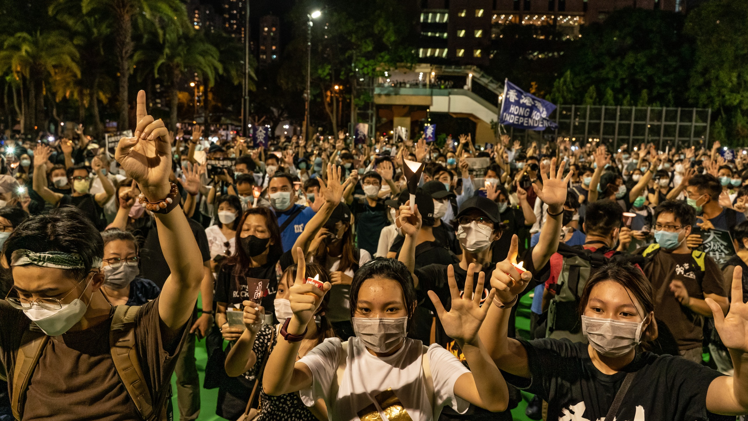 Participants raise their hands as they take part in a memorial vigil in Victoria Park on June 4, 2020, in Hong Kong, China. (Anthony Kwan/Getty Images)