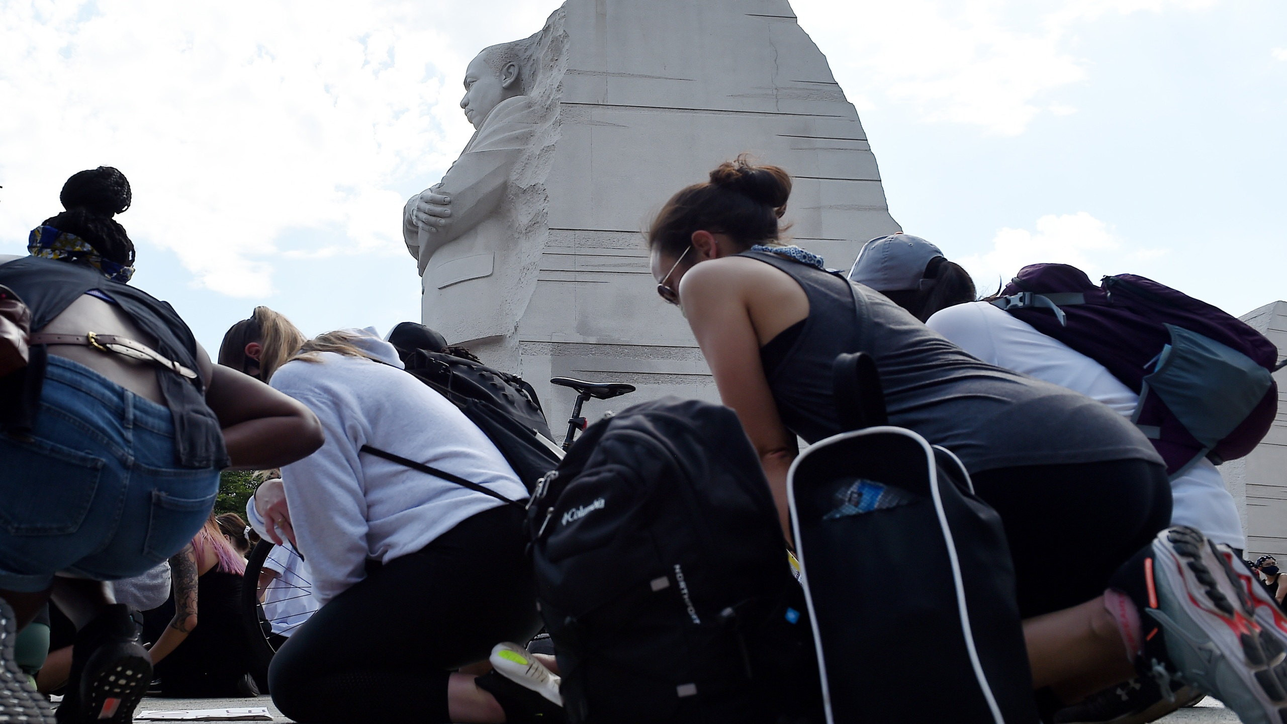 Demonstrators kneel down at The Martin Luther King Jr. Memorial in Washington, D.C., as they protest the death of George Floyd on June 4, 2020. (OLIVIER DOULIERY/AFP via Getty Images)